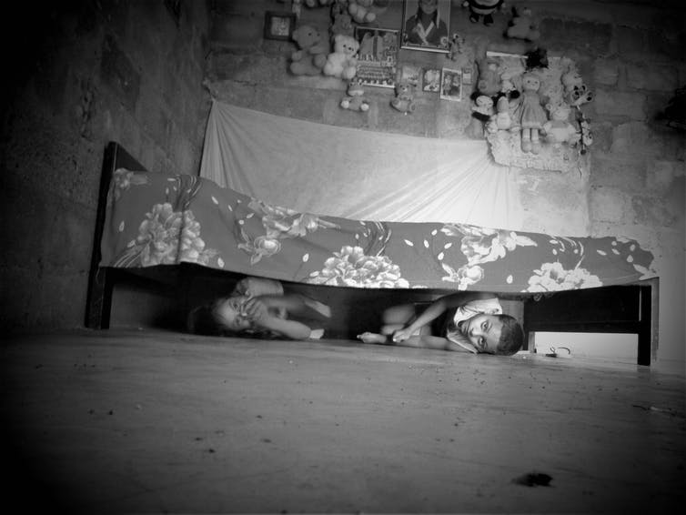 Two children conceal themselves under a bed.