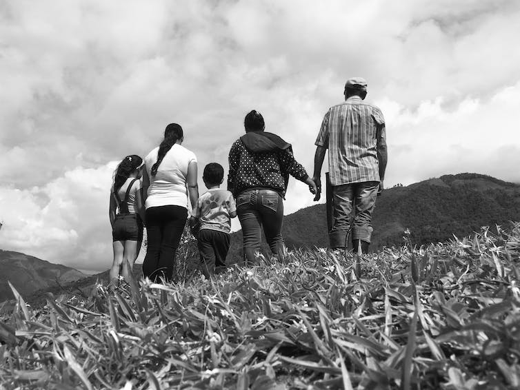 A black-and-white image of people of multiple ages standing in a field, holding hands, with their backs to the camera