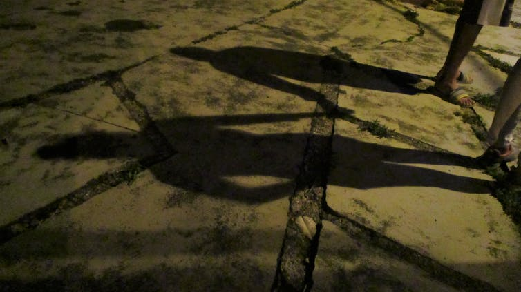 A shadow of people holding hands falls on a paved surface