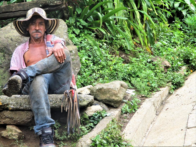 A man in a floppy hat, open shirt, jeans and boots sits on a rock next to greenery