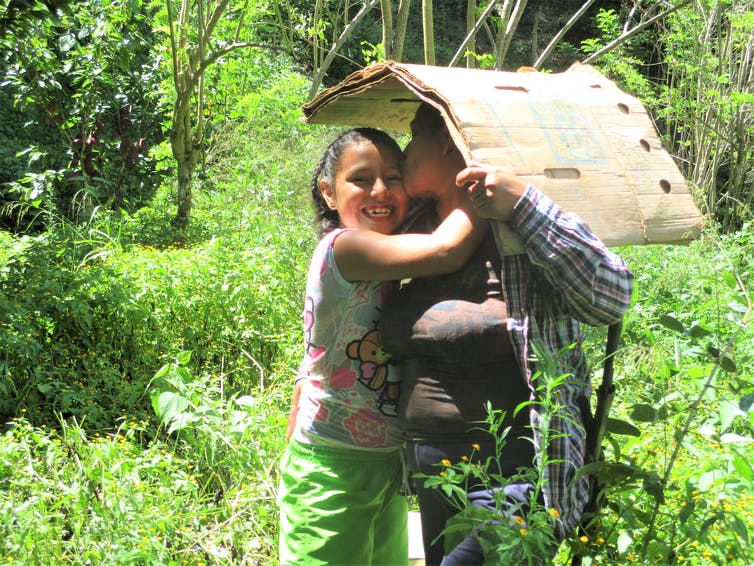 A person holding cardboard overhead hugs a smiling child.