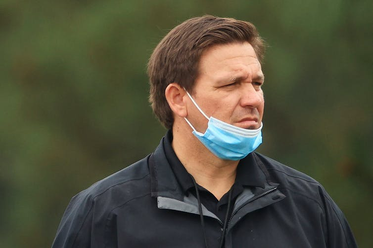 Florida Gov. Ron DeSantis in a black jacket with a mask pushed below his mouth.