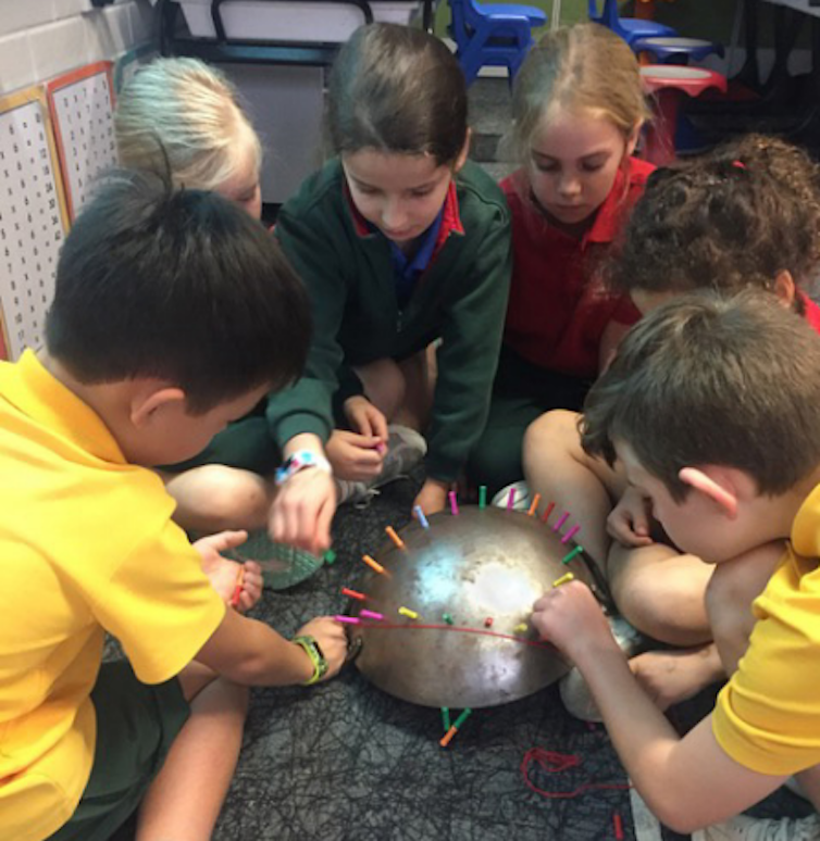 Primary school children moving magnetic pins around a shiny metal domed surface