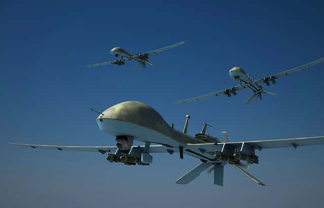 three flying drones armed with missiles
