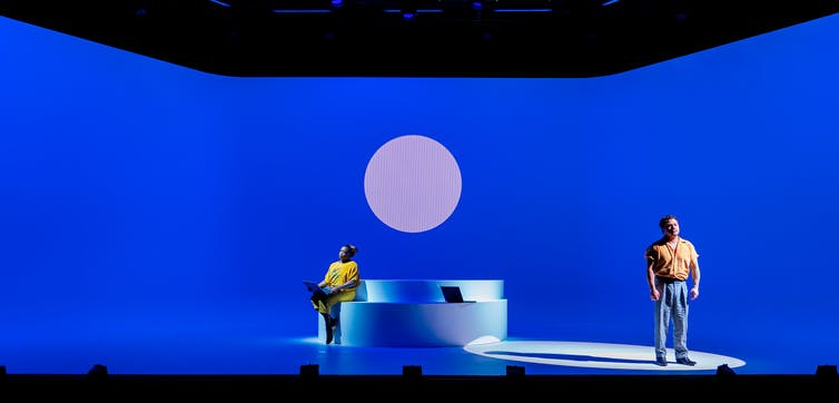 Production image: two people on a blue stage
