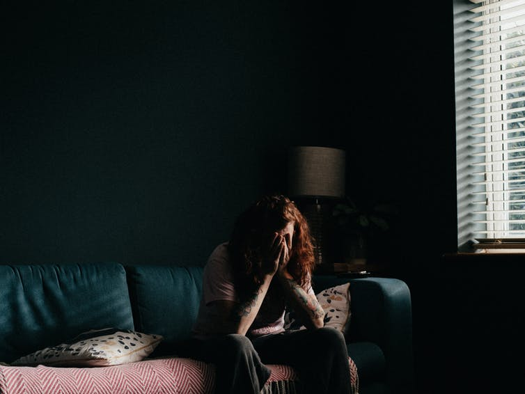 Person sits in a dark room on the couch with their head in their hands.