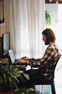 Man sits on computer at home work station.