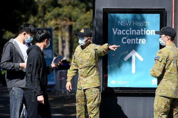 Pessoas sendo encaminhadas a um posto de vacinação por homens em uniformes do exército