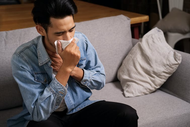 A man sits on a couch, coughing into a tissue.