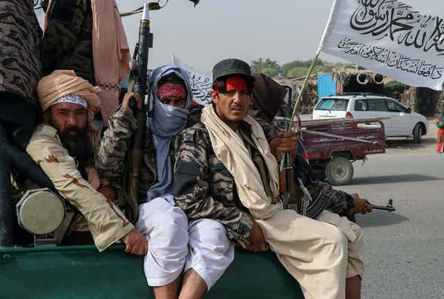 Taliban fighters holding guns and a flag on the back of a truck.