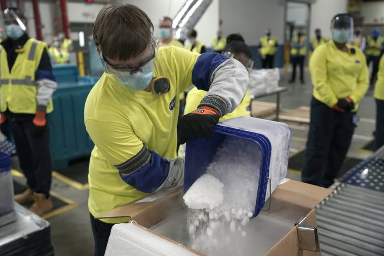 A man wearing protective gear and a yellow shirt dumps dry ice into a box containing Pfizer vaccines