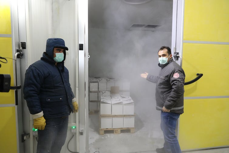 Two men stand next to a cold storage warehouse that contains boxes of Pfizer vaccine.