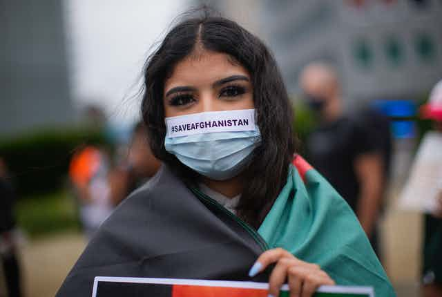 A woman wears a protective face mask reading #SAVEAFGANISTAN during a protest