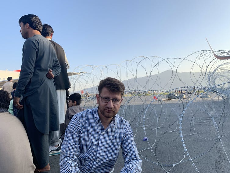 Hanif Sufizada sitting in front of barbed wire at the edge of an airport tarmac.