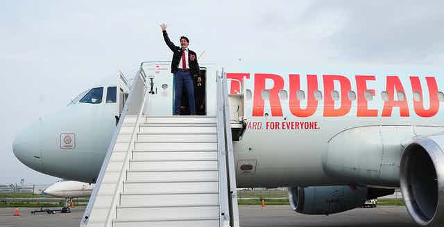 Trudeau is waving from the top of the stairs as he prepares to board his campaign plane that has the word TRUDEAU painted on it.