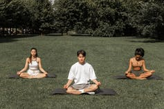 Three people meditating in a park