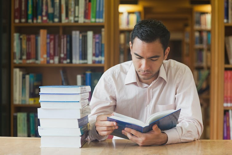Male student reads a book with a pile of other books next to hhim