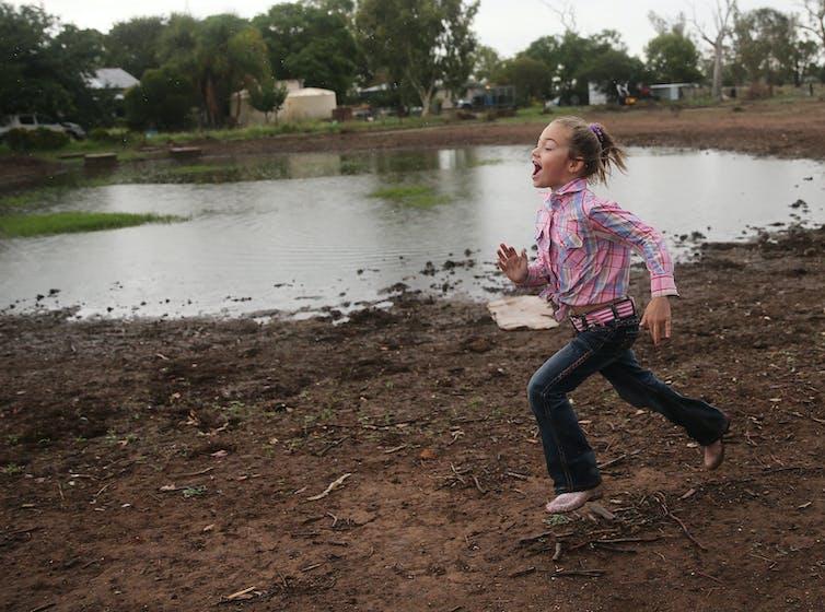 girl runs past dam