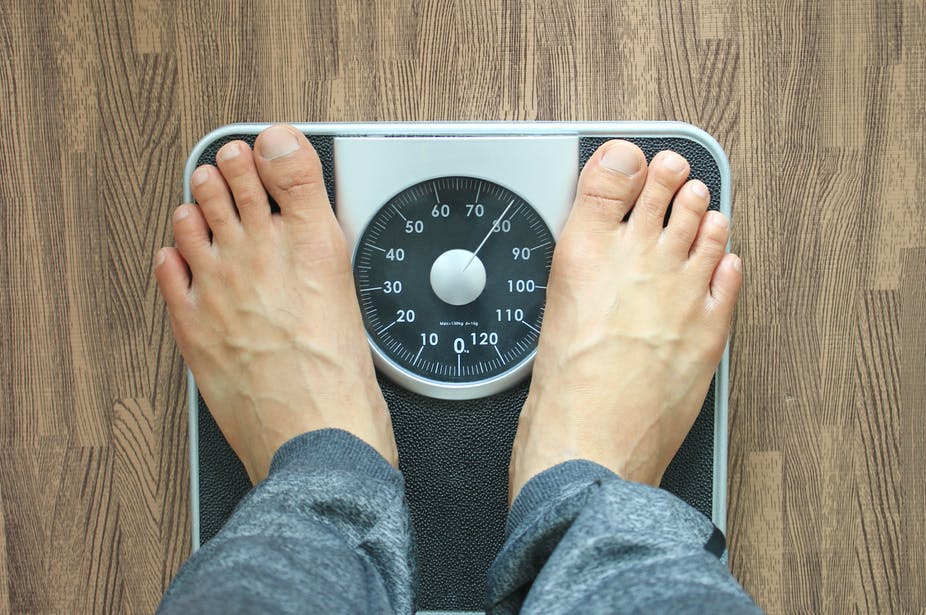 A person with bare feet stands on a scale to measure their weight.
