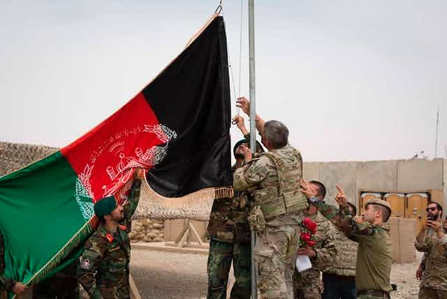 A group of people in military uniforms surround a flagpole with the Afghan flag