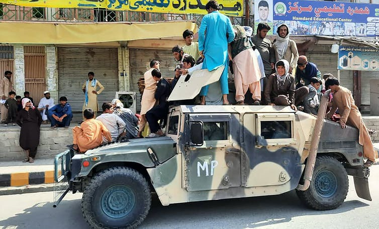 Men in civilian attire stand and sit atop a military vehicle