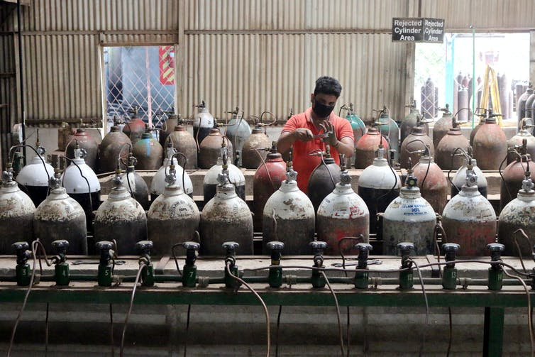 A worker refills oxygen gas tanks in India