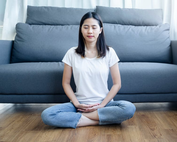 Young Asian woman sitting cross-legged on the floor with her eyes closed.