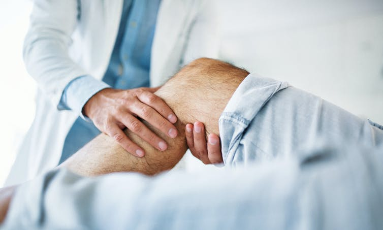 Health care provider holding a person's bent leg below the knee.
