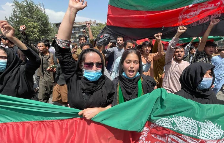 A group of protesters march with Afghan flags