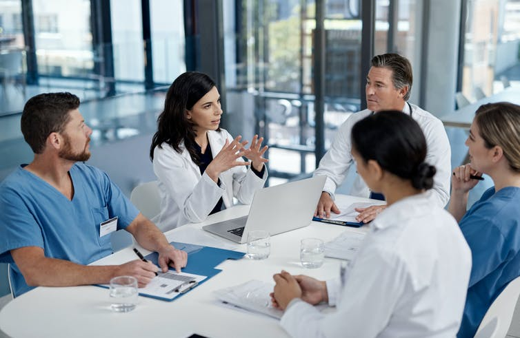 Group of five health care providers sitting around a table in discussion.