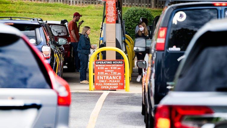 Hileras de coches esperan bombas de gasolina en una concurrida estación.