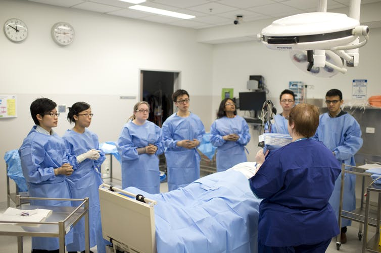 medical students observe surgery in a hospital