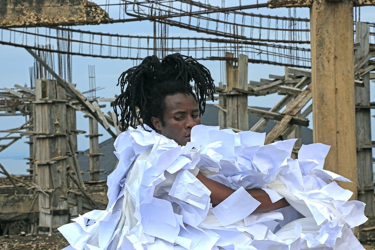 A man at a construction site, his hair a cascade of dreadlocks, he is wrapped in a cloak made of multiple sheets of white paper.