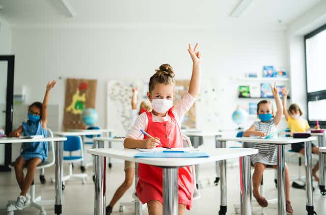 Children with facemasks in classroom