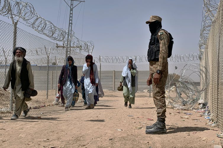 Four Afghan refugees enter Pakistan at a border crossing point marked by barbed wire while a man in army dress watches.