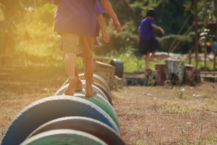 Kids walking on tyres in playground.