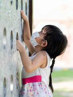 Little girl climbing playground wall with mask on.