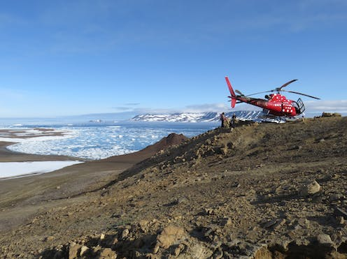 A helicopter parked on a hill with geologists. In the background a small island and packice fills the bay