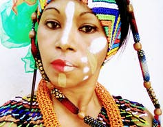 a woman's face with ethnic make-up smears in tan and white, a brightly coloured scarf in her hair matches her jewellery.