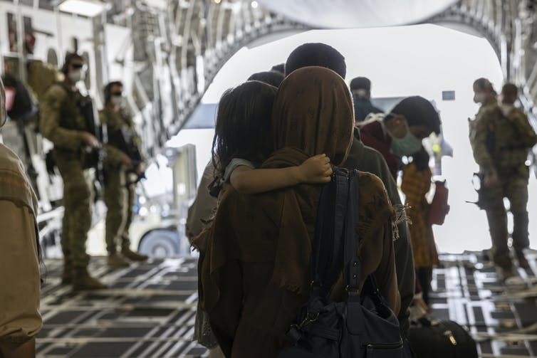 Afghan mother and child leave an ADF flight to Australia.
