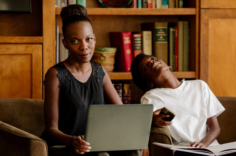 A Black mother holding a laptop computer in her living room looks exasperated while her tired-looking preteen son sits nearby.