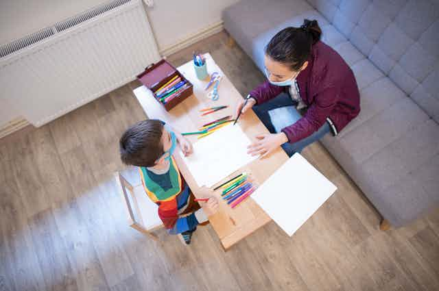 Child and therapist draw together at table