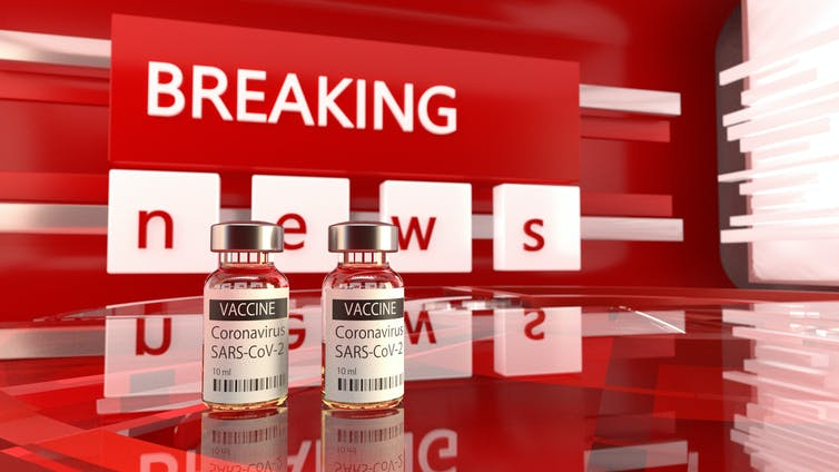 Red breaking news banner behind two vials of COVID-19 vaccine.