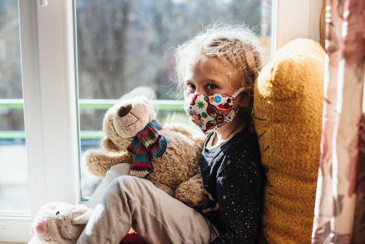 Une jeune enfant portant un masque anti-Covid-19 et un ours en peluche