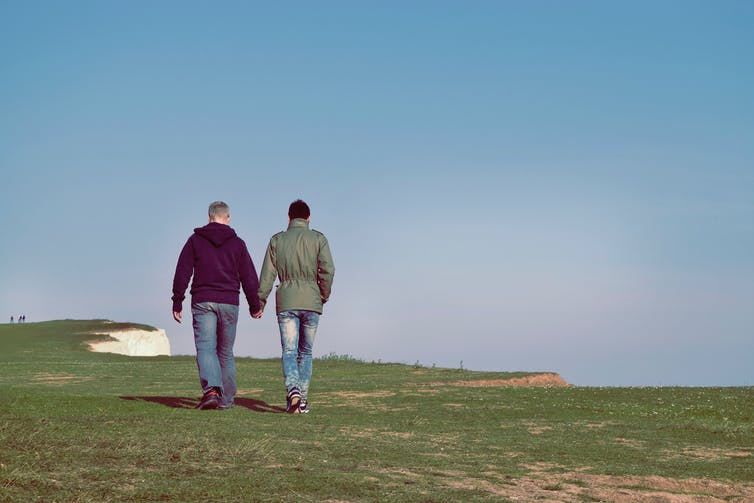 Two men hold hands while walking on grass