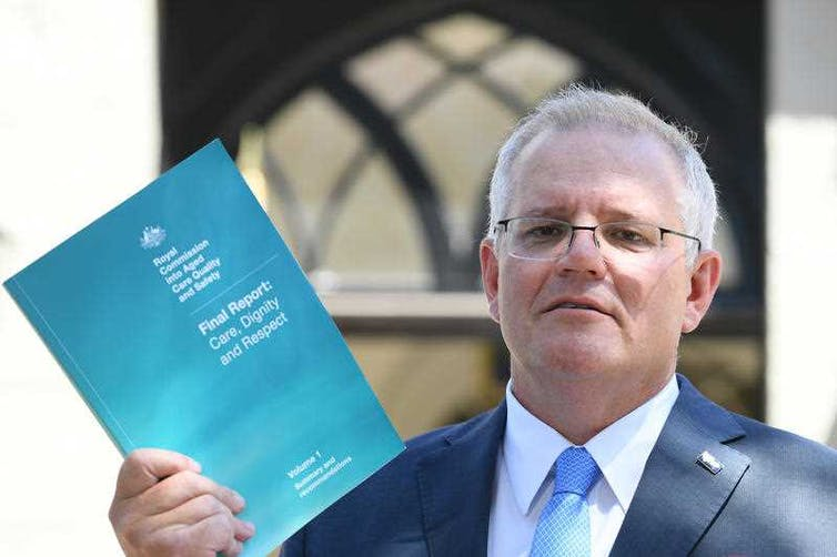 Prime Minister Scott Morrison holding the final report of the royal commission into aged care