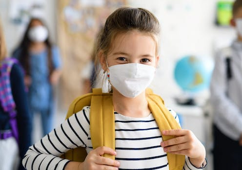 A young girl at school, wearing a backpack and a facemask