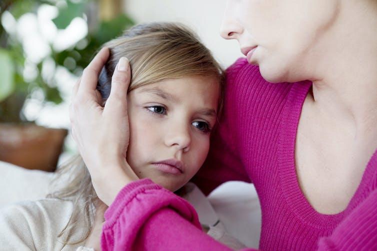 Una niña enferma abrazada por su madre