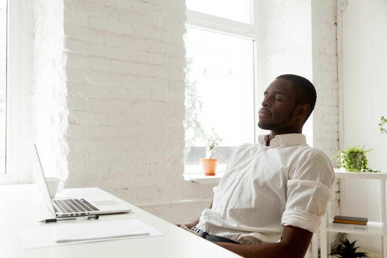 Black man in a white shirt sitting relaxed at a desk with his eyes closed, in a white room with white furniture