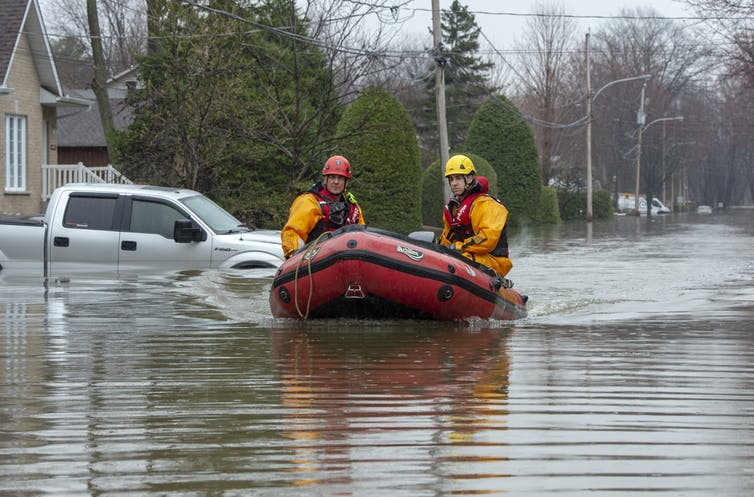 Two men in a dinghy make their way down a flooded street